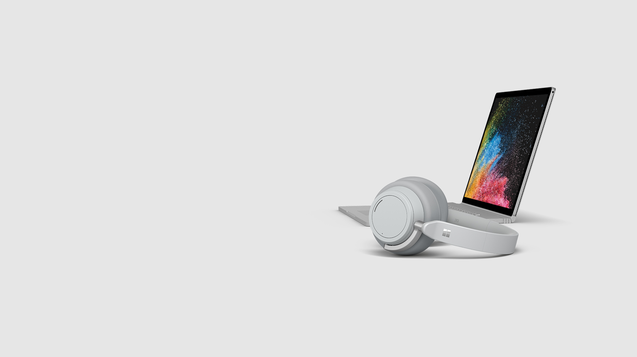 A Surface Book 2 sits with a pair of Surface headphones in front of it