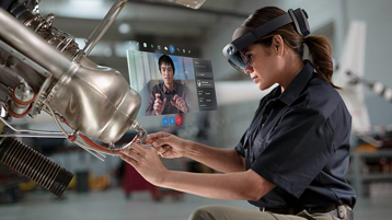 A factory worker wearing a HoloLens 2 headset works on a piece of machinery while a hologram plays instructions next to her