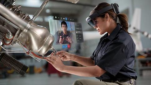 HoloLens 2 ヘッドセットを装着している工場の作業者が、脇のホログラムの説明を見ながら、1 台の機械で作業しています