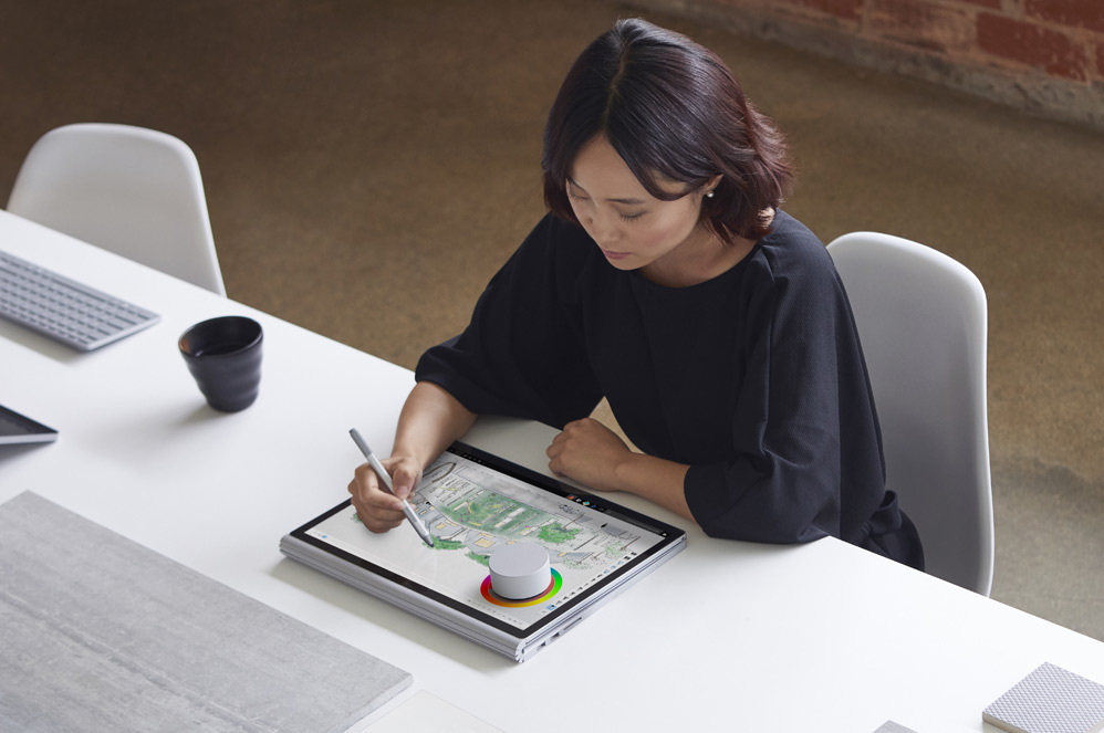 A woman at a desk using Surface Dial and Surface Pen on a Surface Book 2