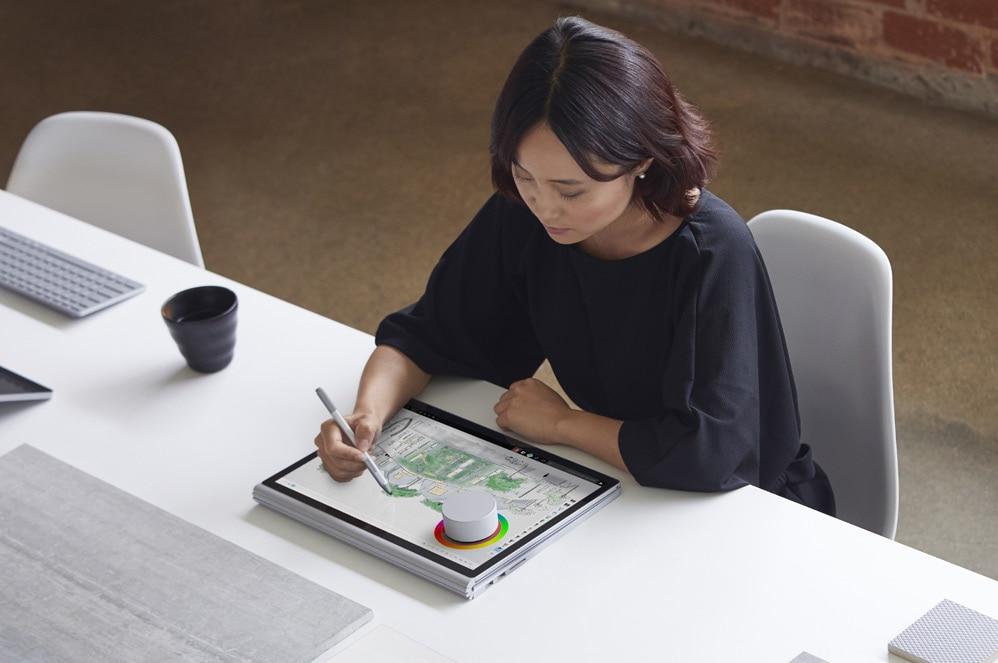 ผู้หญิงคนหนึ่งนั่งอยู่ที่โต๊ะ ใช้ Surface Dial และปากกา Surface กับ Surface Book 2
