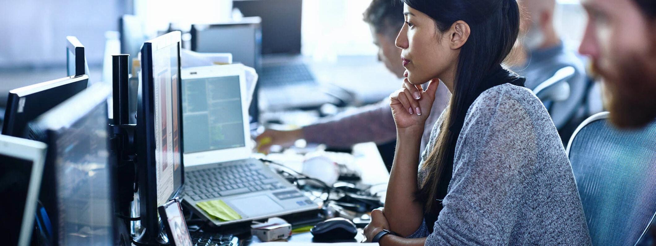 Woman in open office studies monitor.