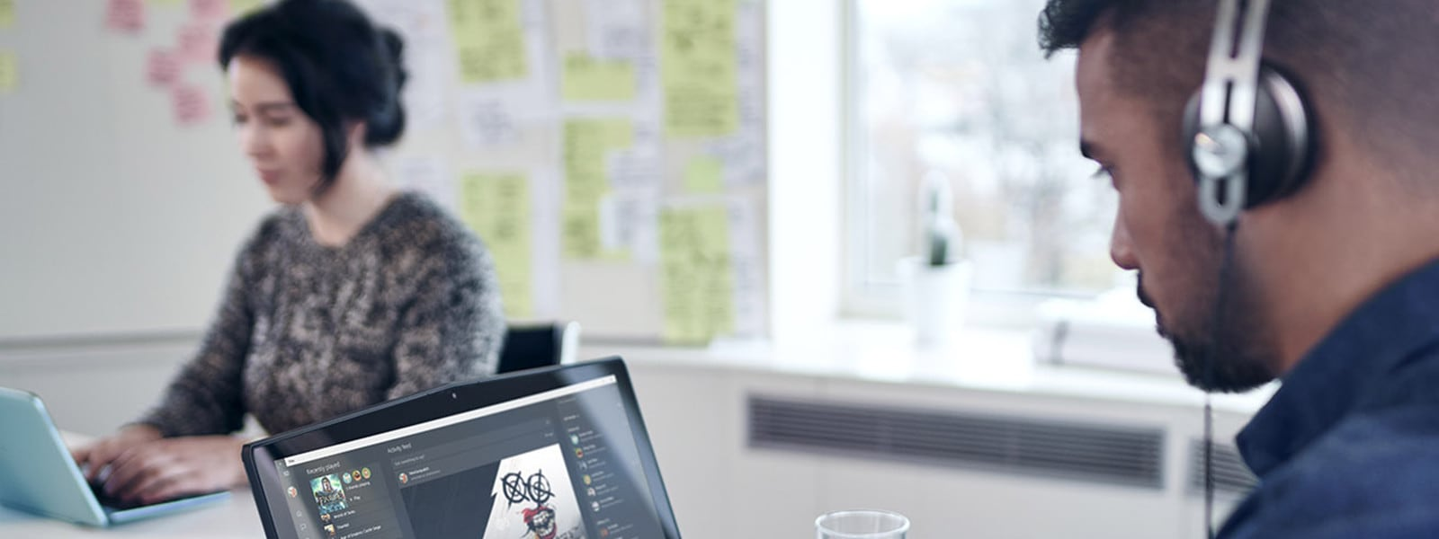 ヘッドホンで音声を聞きながらパソコンを操作している男女2人