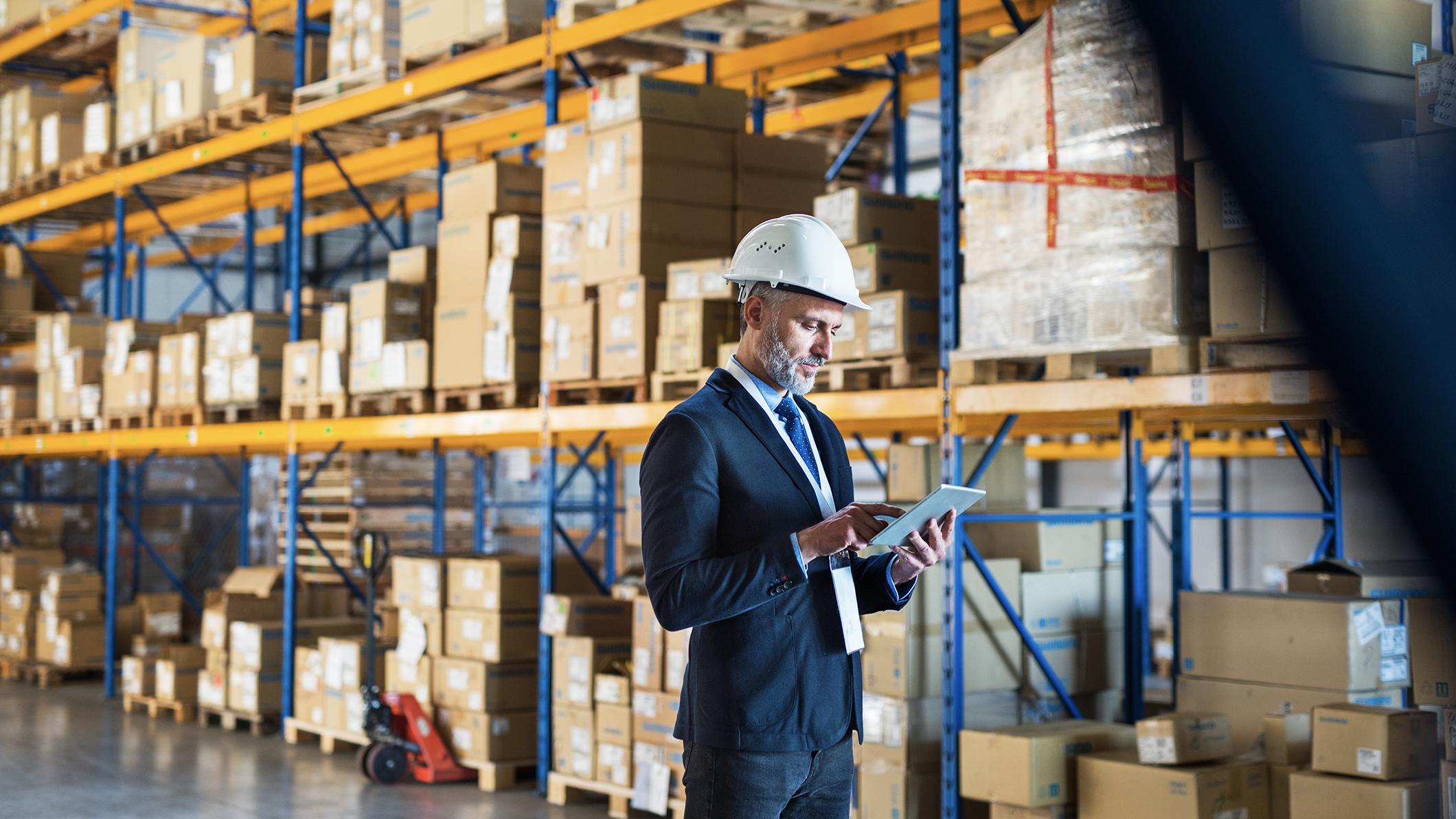 two men wearing hard hats talking in a warehouse