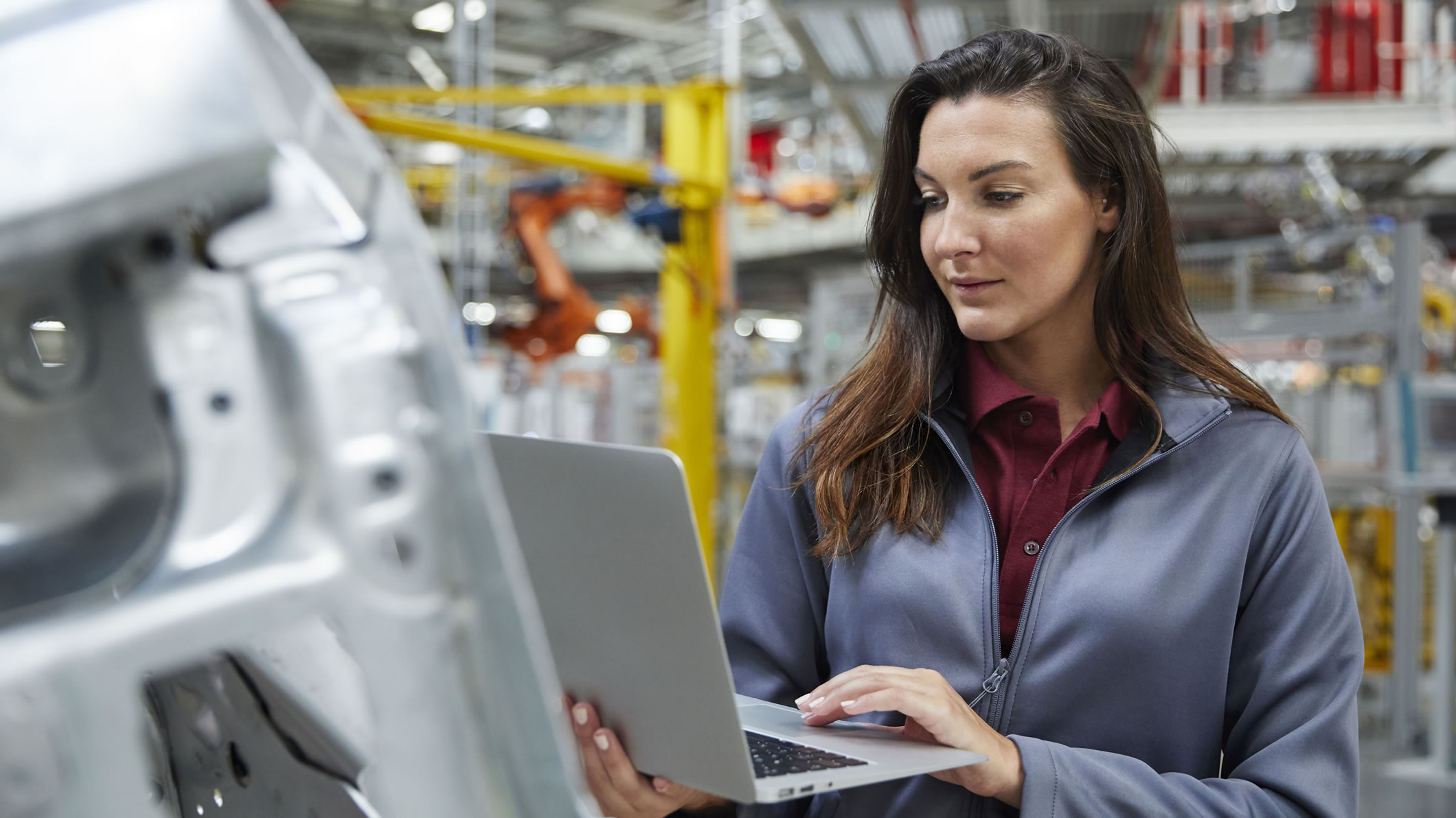 woman using laptop in factory setting