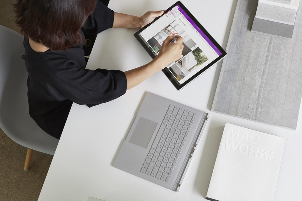 A woman at a desk using Surface Book as a tablet with Surface Pen