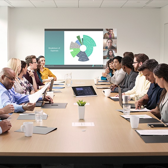Photograph of presentation to people in a large meeting room.