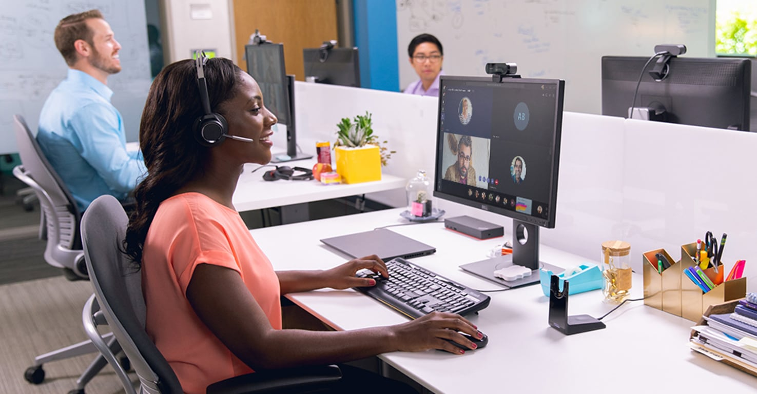 Photograph of a person wearing a headset with a microphone engaged in a Teams video call displayed on their desktop monitor. There are others working at desks in the background.