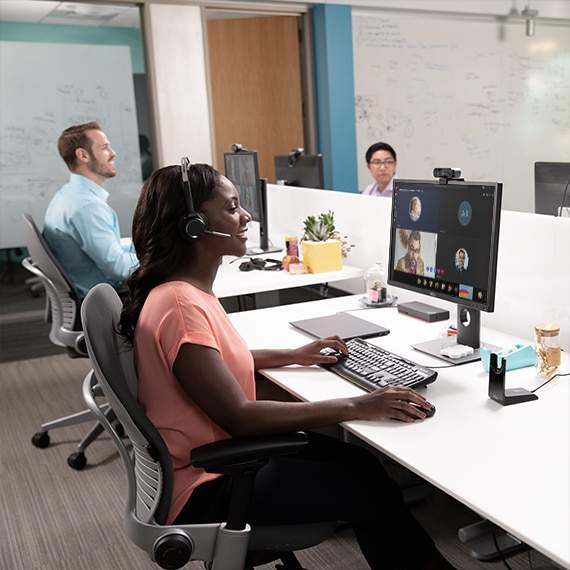 Photograph of a person with a headset in an open office doing a presentation in a Microsoft Teams meeting.