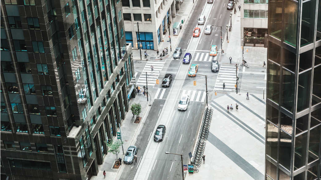 Looking down on a street view between buildings with several cars and bikes and people