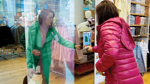 Two woman standing across from each other between glass viewing clothes on a tablet in a retail store setting