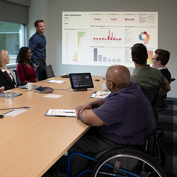 Photograph of person presenting to a group in the meeting room and online