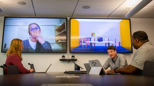 Photo of a dual-screen system in a conference room. On one screen is a live image of a meeting participant. The other screen shows content related to the meeting.