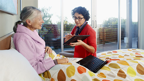 Home healthcare worker using a tablet device to show something to a patient in bed