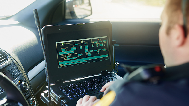 Over-the-shoulder view of a police officer entering information into a database on a laptop computer inside of a vehicle.