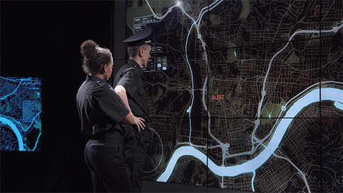 Two uniformed police officers standing in front of a wall projection display of a city map.