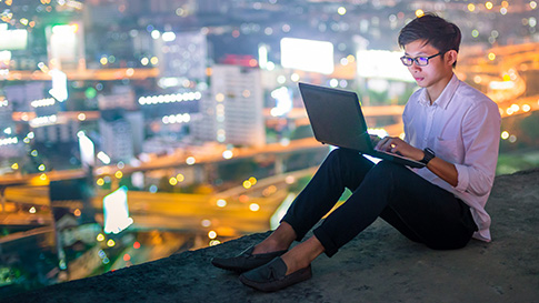 man using laptop outside with view of city skyline behind him
