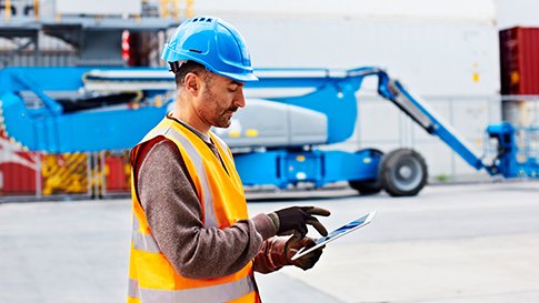 Worker wearing hard hat and safety vest using a tablet device.