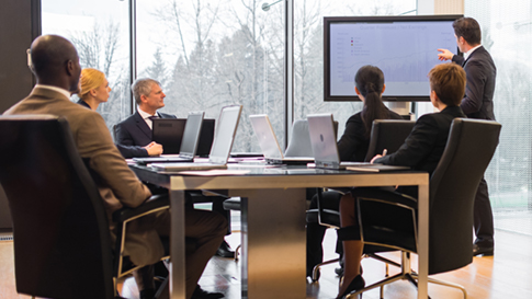 group of business professionals in meeting viewing data charts on large display screen
