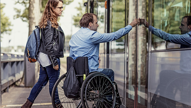 man in wheelchair using public transportation