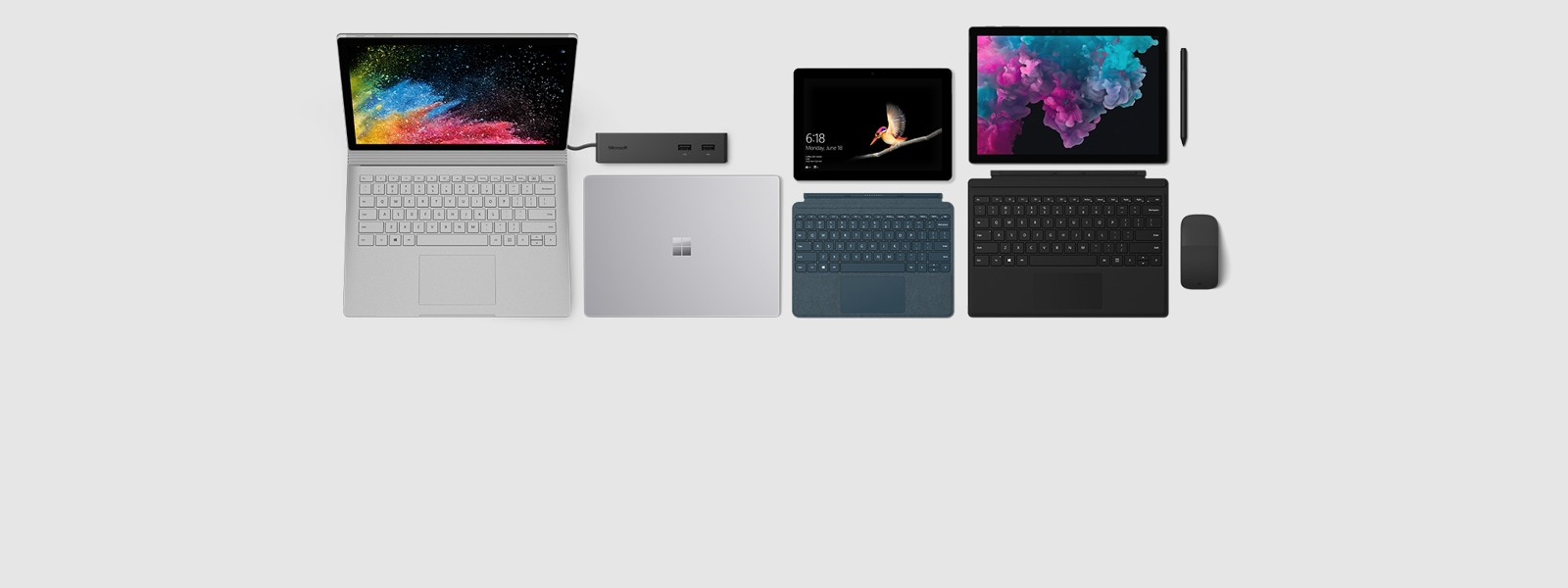 Surface Book, Surface laptop in platinum, Surface dock, Surface Go with Cobalt type cover Surface Pro 6 with black accessories
