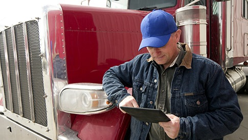man standing in front of long haul truck using tablet