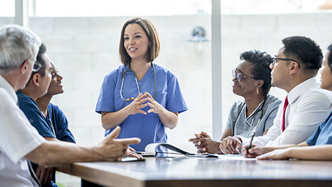 Healthcare worker presenting to a group of others seated at a table.