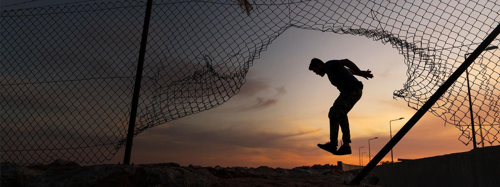 Un hombre que salta junto a una reja a la luz del anochecer