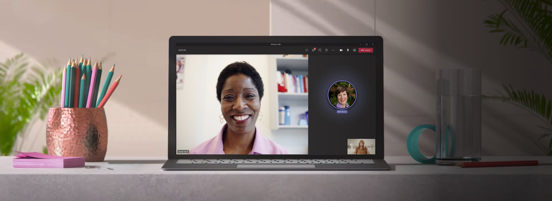 A laptop showing a call between three people on Teams.