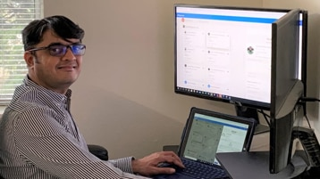 Nirav Khandhedia smiles while working at a desk in a home office.