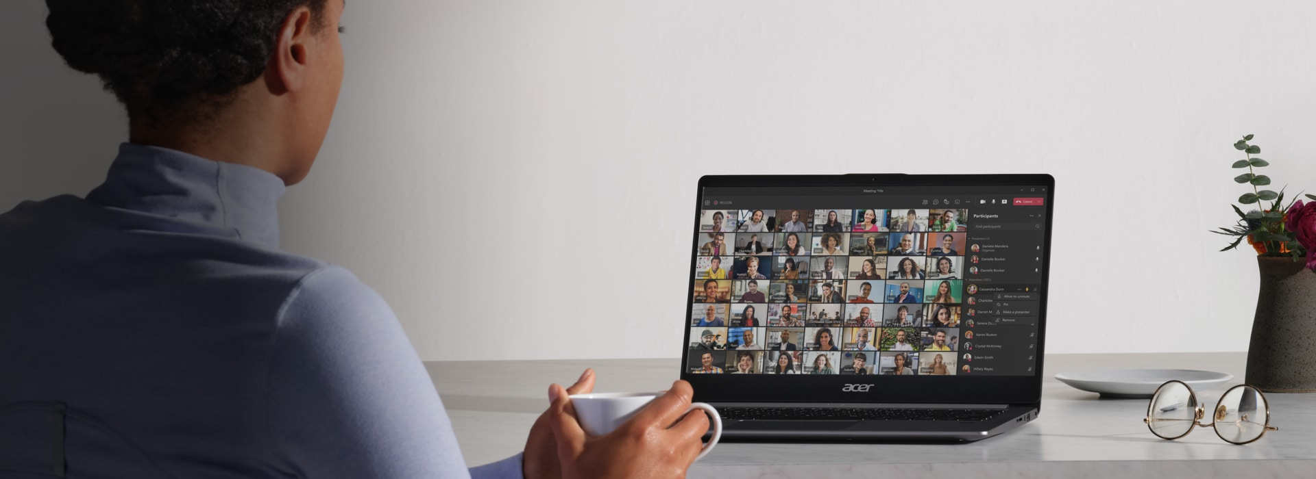 A person holding a coffee mug while on a Teams video call with many participants.