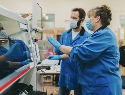 Two people in PPE looking at a machine