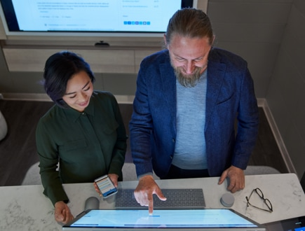Two people using a touchscreen desktop monitor.