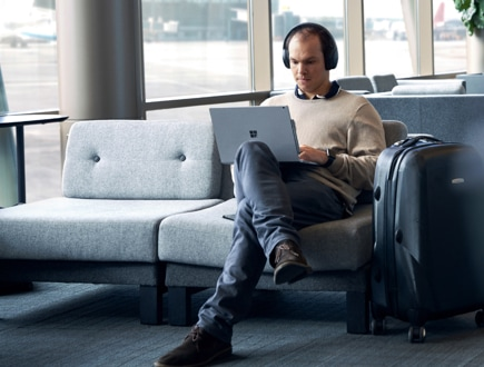A person sitting in an airport using a laptop and headphones.