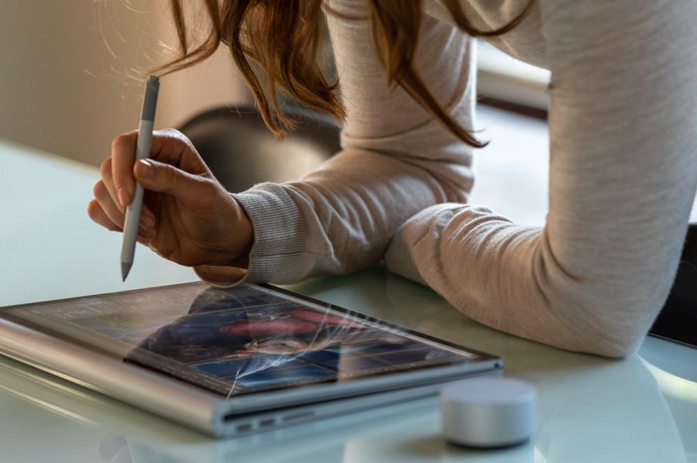 Una mujer usa su Surface Book 3 como tableta, con el Lápiz para Surface y Surface Dial