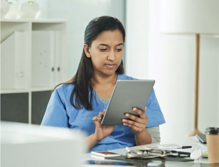 A medical professional using a tablet.