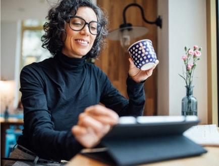 Osoba drží šálek kávy apoužívá tablet.