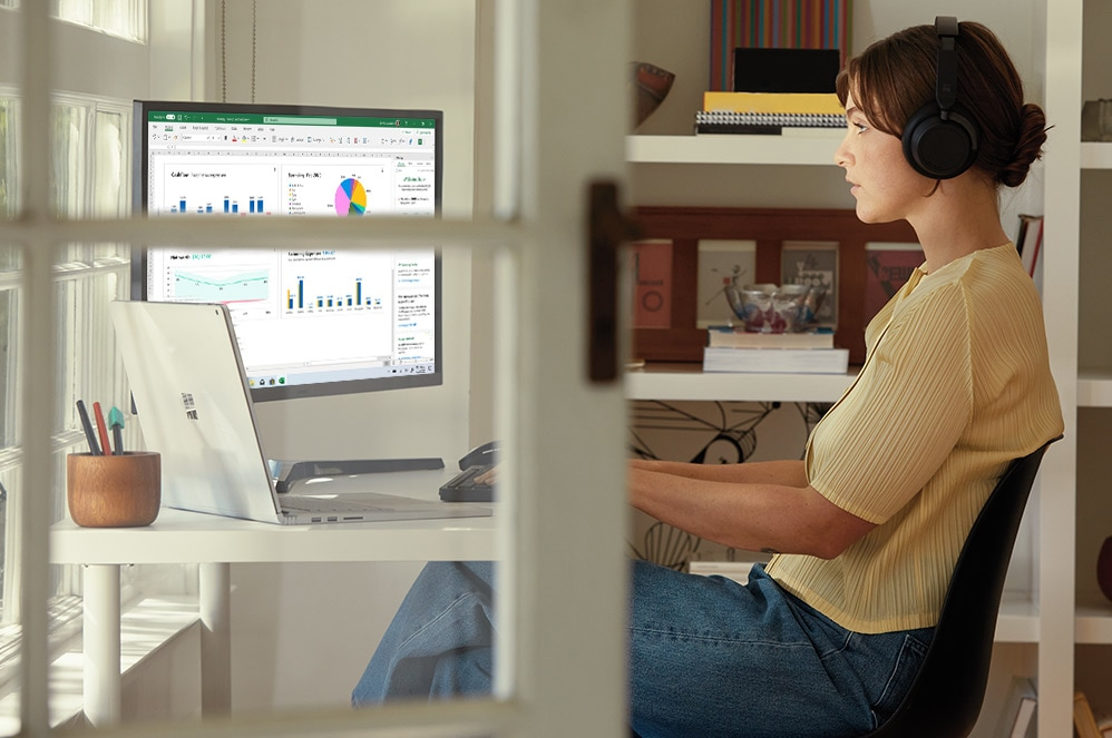 Una mujer lleva puestos auriculares y trabaja en Microsoft Excel