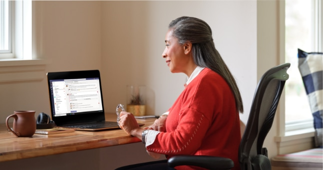 A person sitting at a desk having a text conversation in Teams on their laptop.