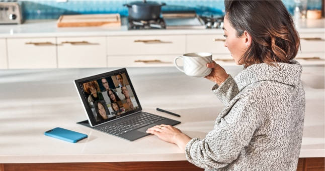 A person sitting at a kitchen counter participating in a Teams video call on a tablet.