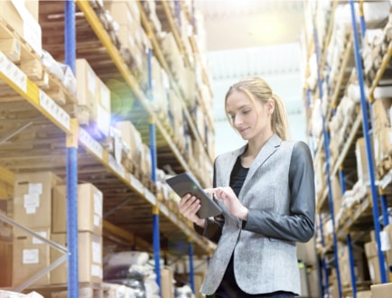 A person in a warehouse holding a tablet.