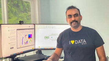 "Kanamarlapudi sits next to a desktop and smiles with a shirt that reads ""I love data."""