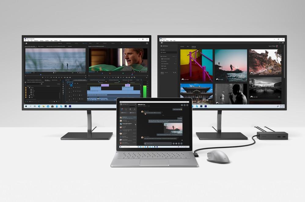 Deux écrans affichant les applications Adobe avec un Book3 à l'avant-plan accompagné d'une souris Surface et d'une station d'accueil.