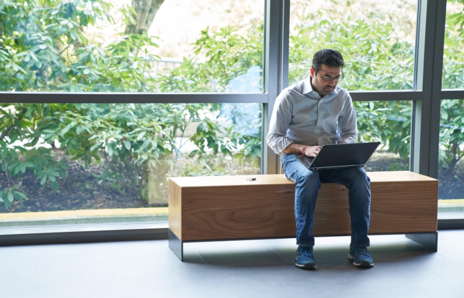 A person sitting on a wooden bench using a laptop on their lap.