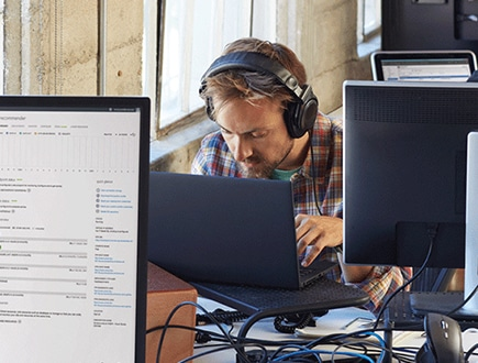 A person wearing headphones looking down and using a laptop.
