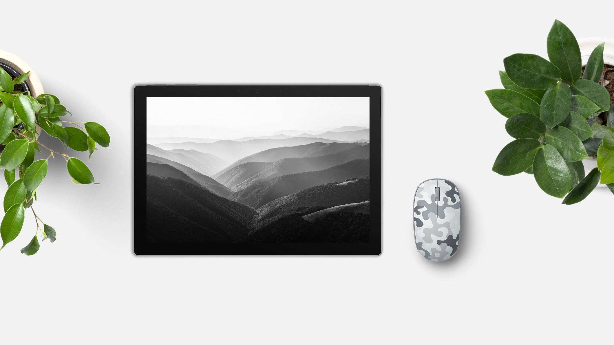 Microsoft Microsoft Bluetooth Mouse Camo Special Edition next to a tablet.