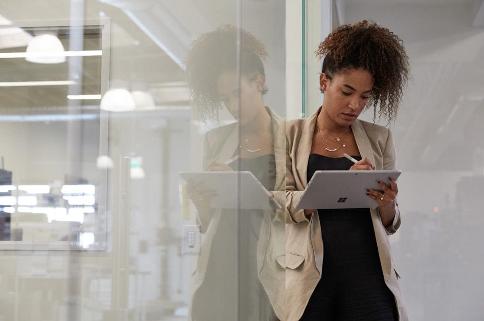 O femeie scrie cu creionul Surface pe o tabletă Surface.