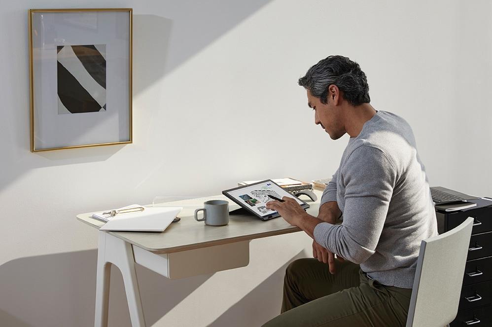 Un bărbat lucrând în biroul de acasă cu creionul Surface pe dispozitivul său Surface Pro