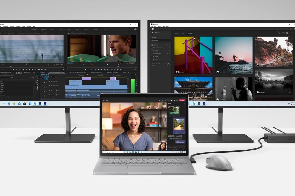 兩台螢幕顯示 Adobe 應用程式,Book 3 與 Surface 滑鼠和擴充基座在最前方
