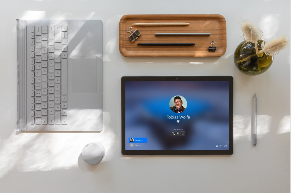 A Surface Book 3 shows the Microsoft Hello Screen surrounded by various Surface accessories